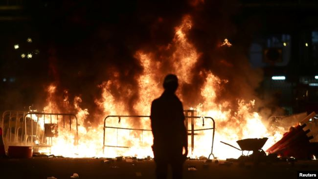 2019年10月4日晚在香港特首宣布将实行禁蒙面法后一名抗议者站在黄大仙区街道上燃烧的一堆火旁。