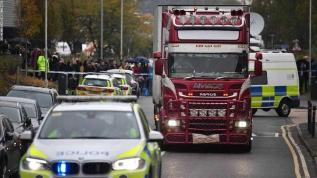 a-truck-driving-down-a-street-next-to-a-car-police-officers-drive-away-a-lorry-c-in-which-39-dead-bo_221238_.jpg