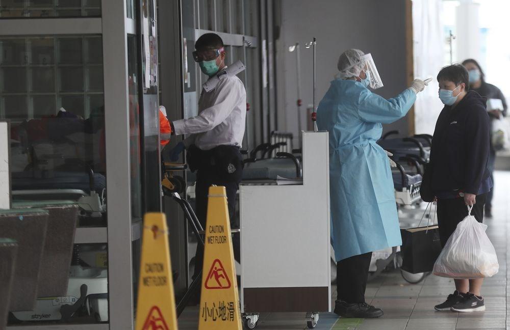 武漢肺炎持續擴散,香港9日新增3名確診病例,其中2例為一名24歲男病患,以及他的90歲祖母,他們家族成員中的另外7人初步確診感染武漢肺炎。圖為身穿防護衣的香港瑪嘉烈醫院人員檢測民眾體溫。(美聯社)