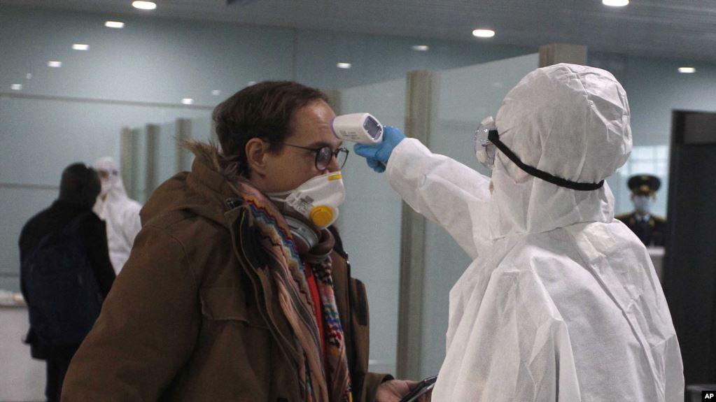 一名戴着口罩的乘客在登上前往符拉迪沃斯托克的飞机之前在平壤国际机场接受体温检查。(2020年3月9日)