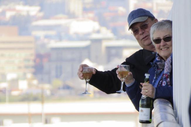 """邮轮""""至尊公主号""""9日终于获准停靠在加州奥克兰港,非美国籍乘客可下船接受检测。一对新泽西州的夫妇高兴举杯,庆祝上岸。(美联社)"""