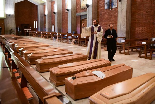 义大利疫情超级惨重,死亡人数破万,图为义大利一座教堂摆满棺材,神父为正为死者祈祷。(Getty Images)