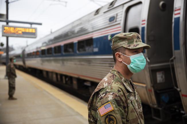 罗德岛州国民兵在美铁车站拦截纽约客,要求他们自行居家隔离。(美联社)