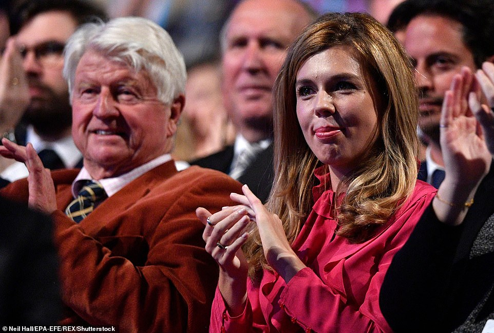 Stanley Johnson (L) and Carrie Symonds (R), father and girlfriend of Britain's Prime Minister Boris Johnson, watch as he delivers his keynote speech at the Conservative Party Conference