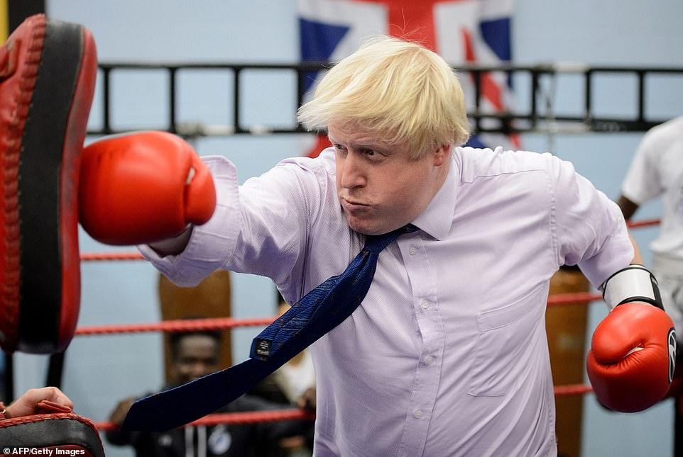Boris Johnson boxes with a trainer during his visit to Fight for Peace Academy in North Woolwich, London, 2014 while he was mayor of London