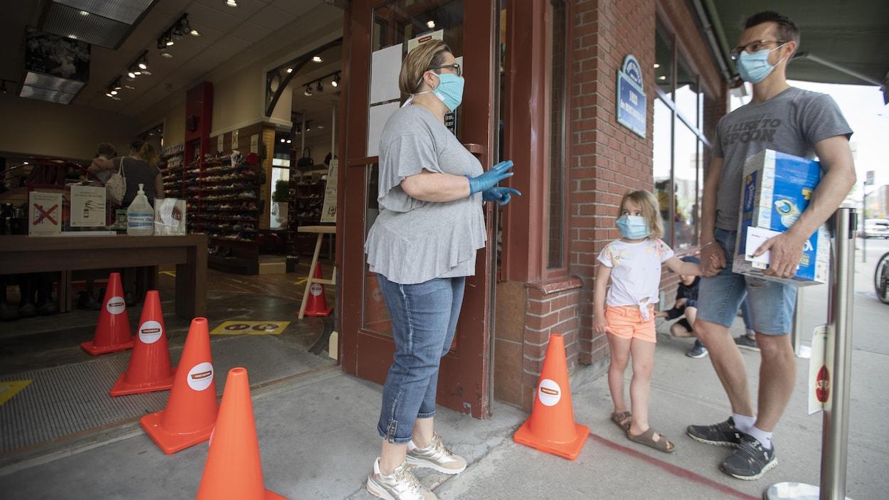 Un homme et sa fille portant un masque attendent pour entrer dans un magasin.