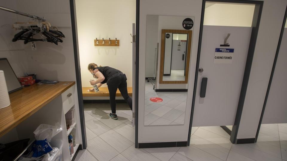 Une femme nettoie une cabine d'essayage.