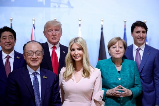 """伊万卡的工作曾被质疑超出其权限。她在2017年G20汉堡峰会上,坐在本来供国家首脑就座的位置上""""代父开会"""",引发争议。图为伊万卡2017年7月8日在德国汉堡出�女性企业家融资活动,该话动是G20峰会进行期间同时举行的活动。以伊万卡的职级站在一众世界领袖当�,看来有点突兀。(Reuters)"""
