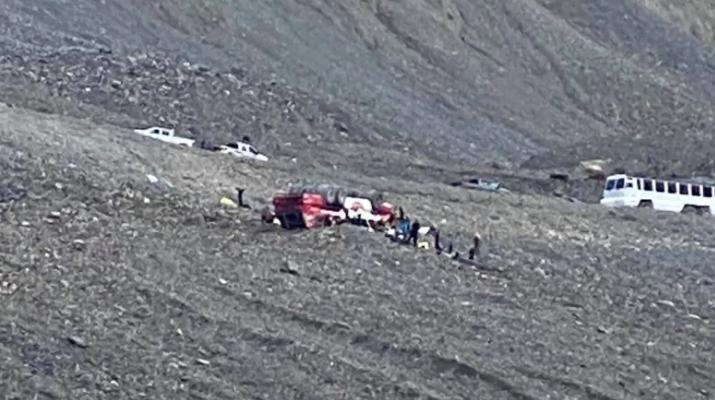圖中央紅白相間的觀光巴士翻入斜坡,並導致多人死傷。CBC/ Randy Cusack