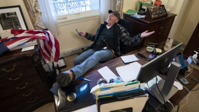 A supporter of US President Donald Trump sits at a desk in Congress building